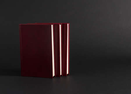 books with red cover on black background, isolated. back to school