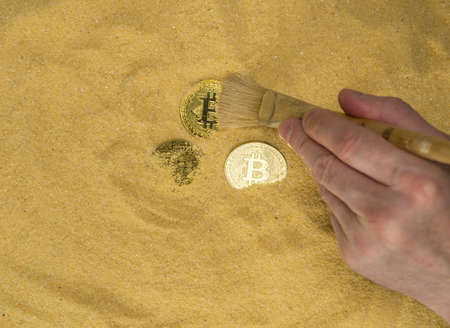 an archaeologist with a brush clears the bitcoin coin on the golden sand. top view. finding and mining cryptocurrency Stock Photo