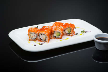 sushi in a plate on a black background with reflection. fish roll Reklamní fotografie