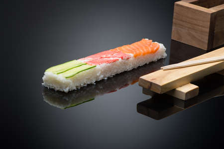 sushi on black background with chopsticks. wooden press form for making sushi Reklamní fotografie