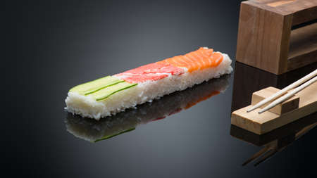 sushi on black background with chopsticks. wooden press form for making sushi Reklamní fotografie - 129551461