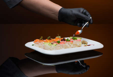 chef decorates sushi with caviar. process of cooking sushi