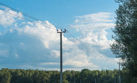 old high-voltage tower against the blue sky in the countryside