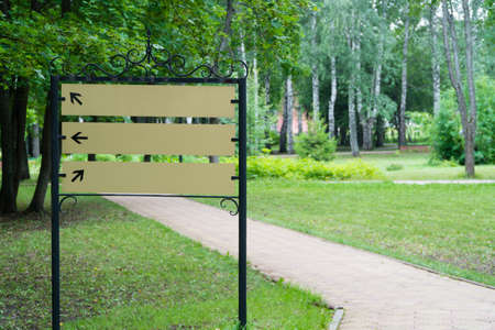 blank sign in the park by the path on the background of trees Reklamní fotografie