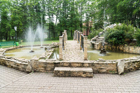 fountain and bridge of stone tiles in the Park. a decorative pond outdoors