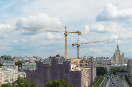 construction cranes in the urban landscape against the sky