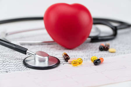 Stethoscope on electrocardiogram, and toy heart. Concept healthcare. Cardiology - care of the heart