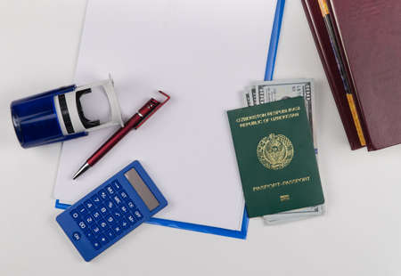 Uzbekistan passport with US dollars on the background of documents and contract. Concept - briber and corruption