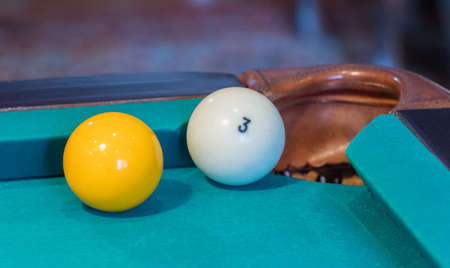 Green billiard table with white balls. Ball at the hole. Closeup  写真素材