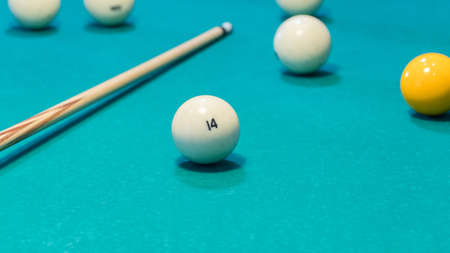 Green billiard table with white balls and cue. Closeup