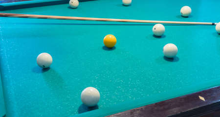 Green billiard table with white balls and cue