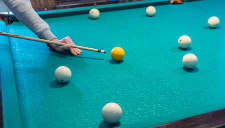 Green billiard table with white balls. Young man playing billiards Foto de archivo - 138084608