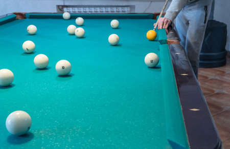 Green billiard table with white balls. Young man playing billiards