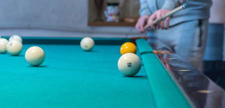 Green billiard table with white balls. Young man playing billiards Foto de archivo - 138087321