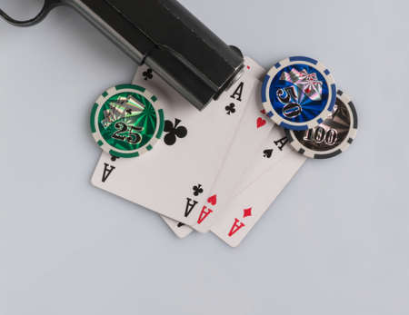Poker chips, cards and gun on a white background. The concept of gambling and entertainment. Casino and poker Foto de archivo - 138287660