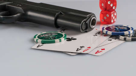 Poker chips, cards and gun on a white background. The concept of gambling and entertainment. Casino and poker Foto de archivo - 138287834