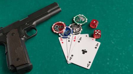 Poker chips, cards and gun on a green background. The concept of gambling and entertainment. Casino and poker Foto de archivo - 138286926