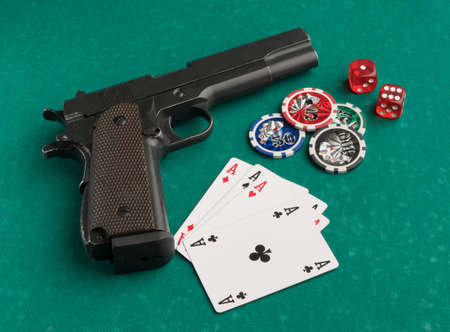 Poker chips, cards and gun on a green background. The concept of gambling and entertainment. Casino and poker Foto de archivo - 138287860