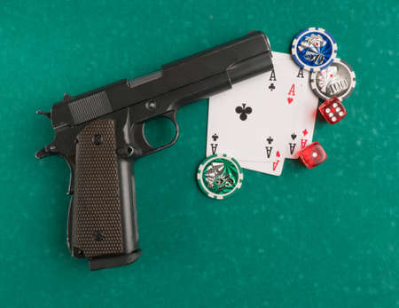 Poker chips, cards and gun on a green background. The concept of gambling and entertainment. Casino and poker Foto de archivo - 138288139