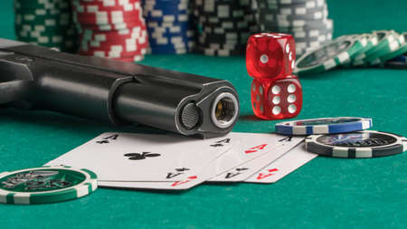 Poker chips, cards and gun on a green background. The concept of gambling and entertainment. Casino and poker Foto de archivo - 138287608