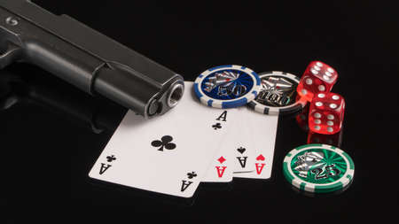 Poker chips, cards and a gun on a black background. The concept of gambling and entertainment. Casino and poker Foto de archivo - 138288158