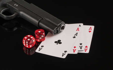 Cards, dice and a gun on a black background. The concept of gambling and entertainment. Casino and poker Foto de archivo - 138288315