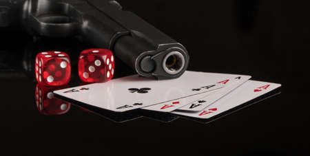 Cards, dice and a gun on a black background. The concept of gambling and entertainment. Casino and poker Foto de archivo - 138287978