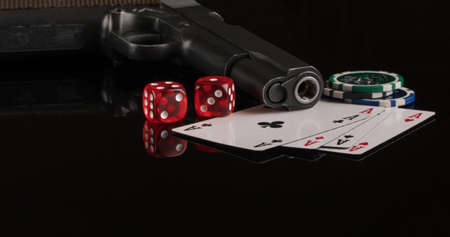 Poker chips, cards and a gun on a black background. The concept of gambling and entertainment. Casino and poker Foto de archivo - 138288323