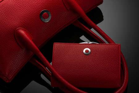 Modische rote Damentasche und Geldbörse auf dunklem Hintergrund Standard-Bild
