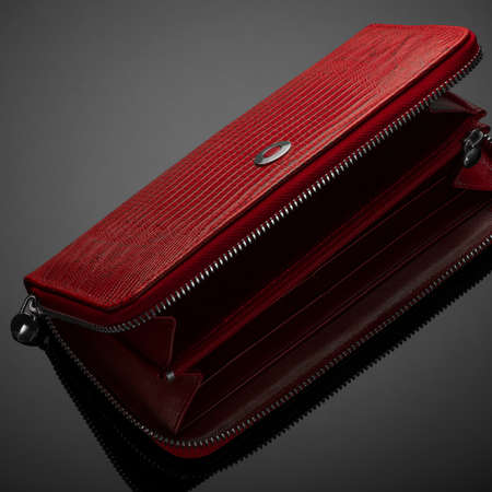 Fashionable red leather women's wallet on a dark background
