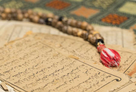 Muslim prayer beads with ancient pages from the Koran. Islamic and Muslim concepts. Ancient old sheets of paper from the Arabic book