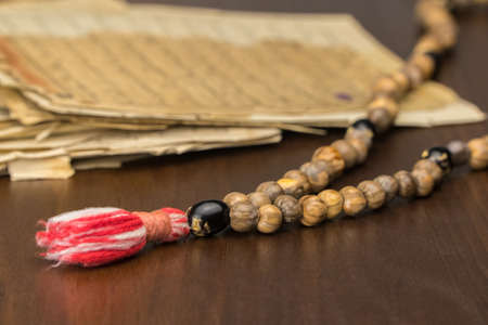 Muslim prayer beads with ancient pages from the Koran. Islamic and Muslim concepts. Ancient old sheets of paper from the Arabic book Stockfoto