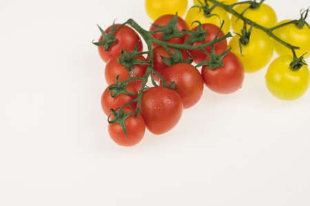 fresh red and yellow cherry tomatoes on a white background. wet tomatoes