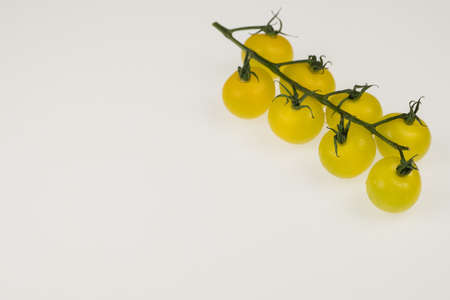 fresh yellow cherry tomatoes on a white background. wet tomatoes