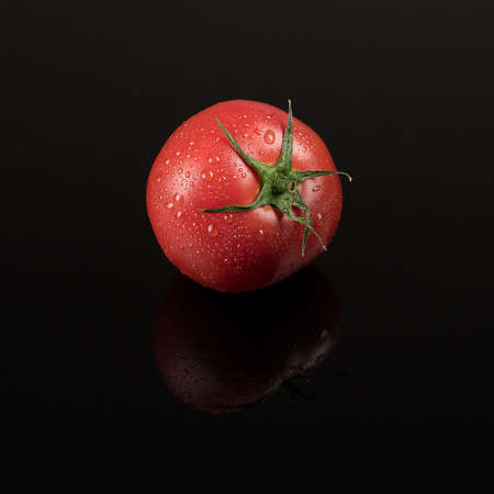 fresh wet tomato on black background with reflection