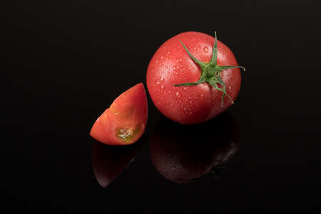 fresh wet tomatoes on a black background with reflection. sliced tomatoes