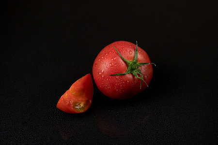fresh wet tomatoes on a black background. sliced tomatoes Фото со стока