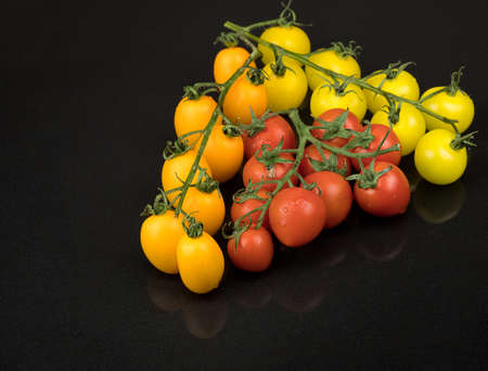 fresh red, yellow and orange cherry tomatoes on a black background with a reflection. wet tomatoes Фото со стока