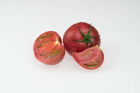 fresh wet tomatoes on a white background. sliced tomatoes