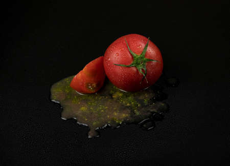 fresh wet tomatoes on a black background. sliced tomatoes with pulp