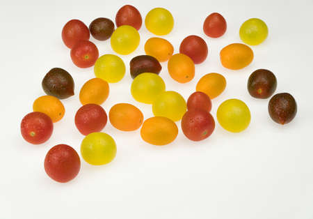 fresh multi-colored cherry tomatoes on a white background. wet tomatoes Фото со стока