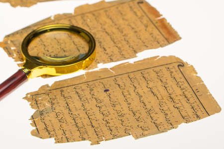 Book pages with an Arabic manuscript on a table with a light and a magnifying glass. Paleography, the study of ancient Arabic writing