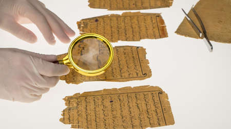A researcher studies Arabic writing from the Koran using a magnifying glass and a table with a light. Paleography, the study of ancient Arabic writing