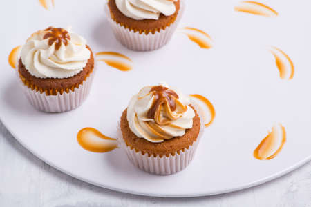 cream cupcake on white plate, top view, close-up