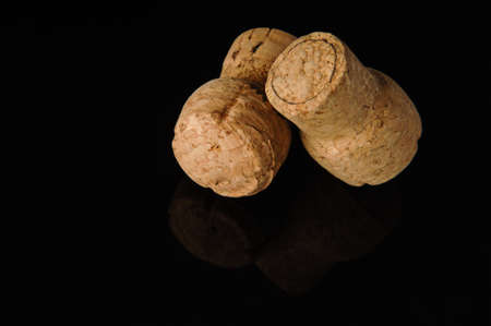 Two old wine corks on a black background with reflection