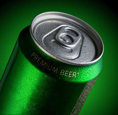 Can of beer with drops of water in a green background with illumination. Advertising of beer