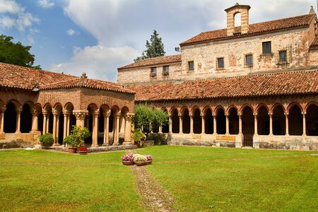 cloister: Cloister of San Zeno Cathedral in Verona showing ornate arches and carvings in summer Stock Photo