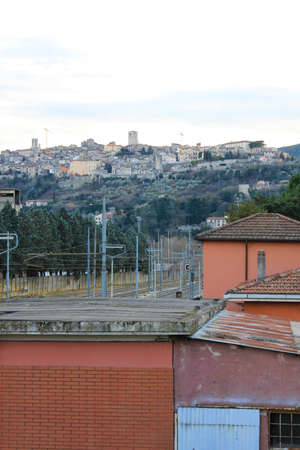 terni day: The medieval village of Narni seen from the train station and the industrial distracted in the valley, Umbria, Italy. Stock Photo