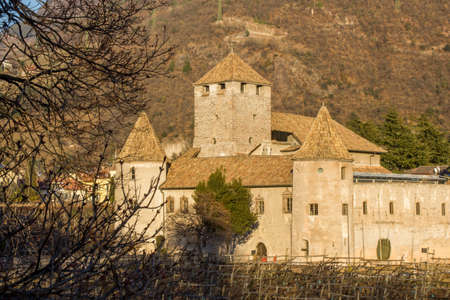 castello: Feudal Maretsch Castle (Castello Mareccio) with its defense wall, round towers, conical roofs, and giant keep surrounded by Tyrolean vineyards and the nearby Dolomite Mountains Stock Photo