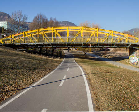 Pedestrian and cycle  yellow steel bridge with mountains in the background.